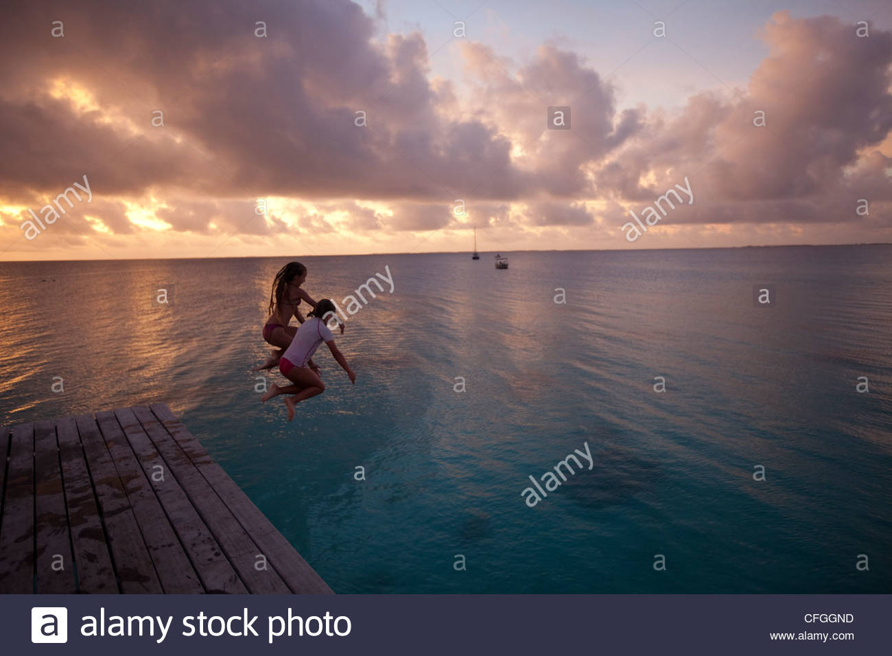 Girls jumping off a pier at the 'Le Maitai Dream' hotel. - Stock