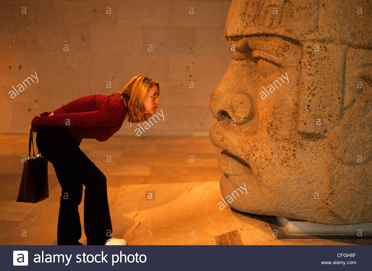 A woman examines an Olmec head in the Museum of Anthropology. - Stock Image