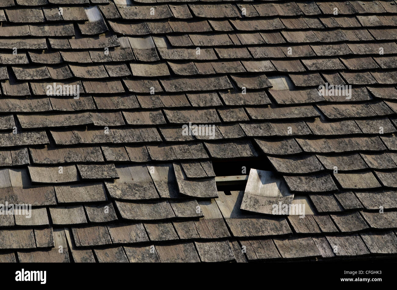 Decaying wood shingle roof. Damaged wood texture, wooden structure. Possible poor workmanship metaphor. - Stock Image