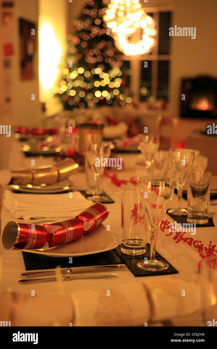 Table laid for Christmas dinner with crackers, christmas tree and decorations - Stock Image