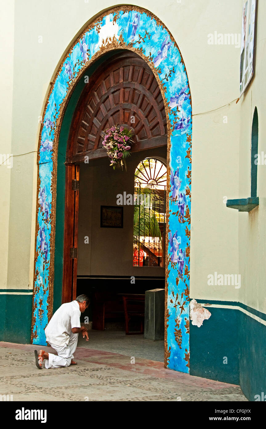 Mexican man in white kneeling in front of a Catholic church in downtown Zihuatanejo, Mexico - Stock Image