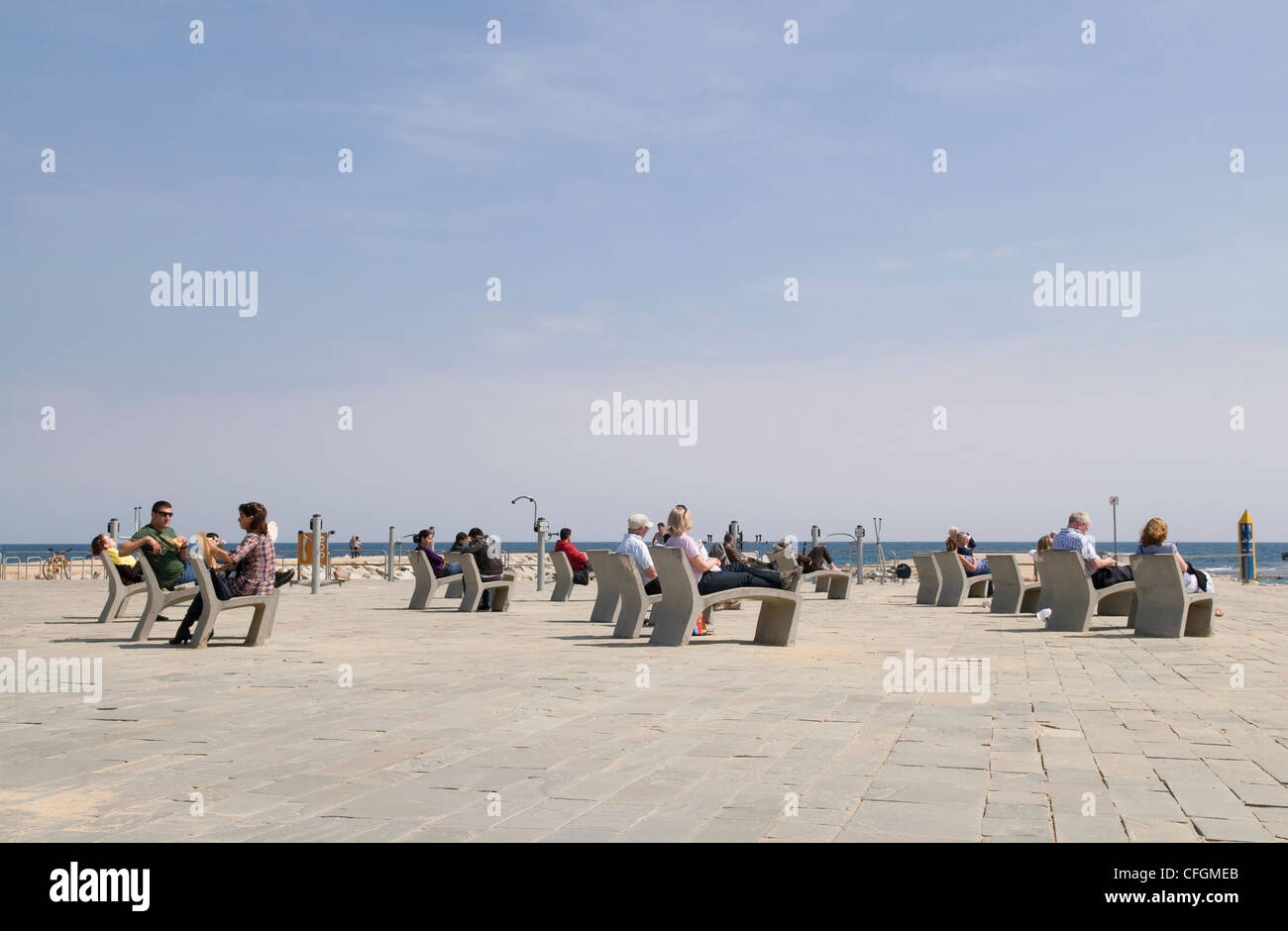 People sitting relaxing on modern concrete chairs in front of the sea in Barcelona, with public exercise machines - Stock Image