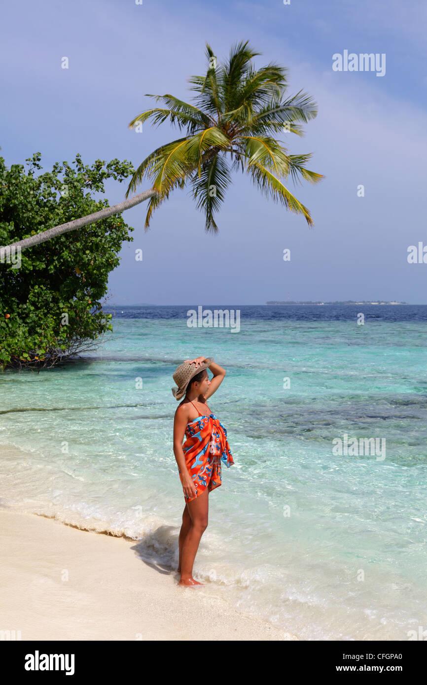 Girl watching the Ocean at the seashore, Biyadhoo island, Maldives - Stock Image