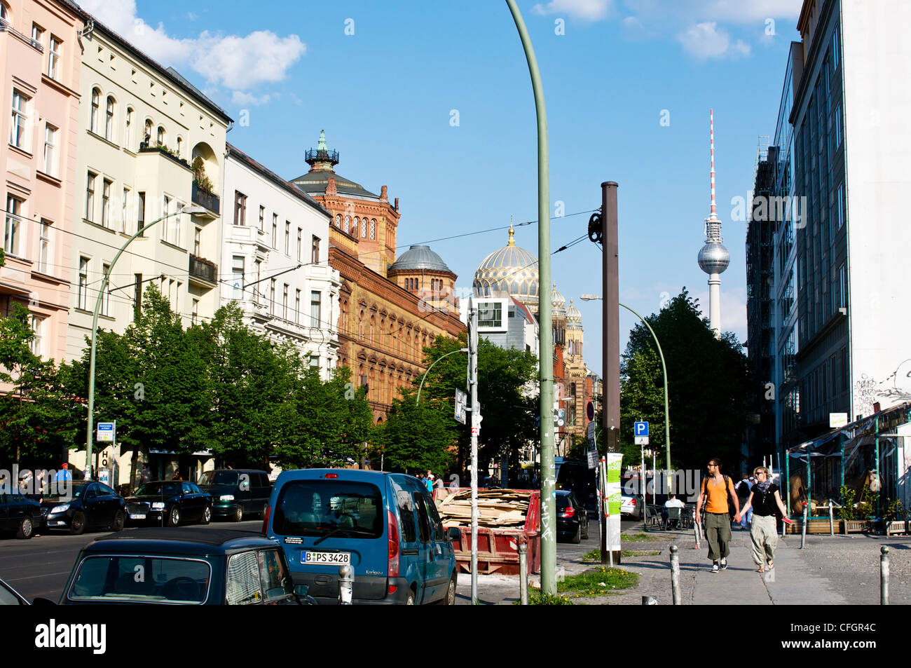 Walking in the sunshine down Oranienburger Strasse in the former East Berlin district of Mitte in Berlin, Germany. - Stock Image