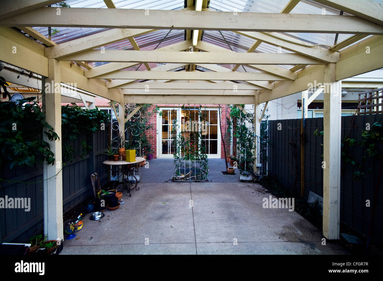 A covered car park and entertainment area at the rear of a townhouse. - Stock Image