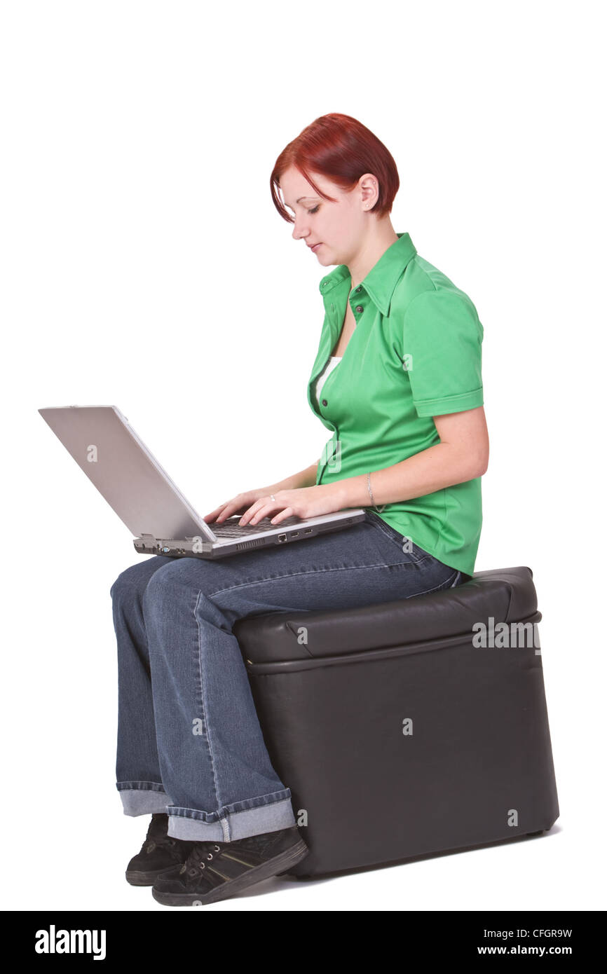 Redheaded girl working on a laptop. - Stock Image
