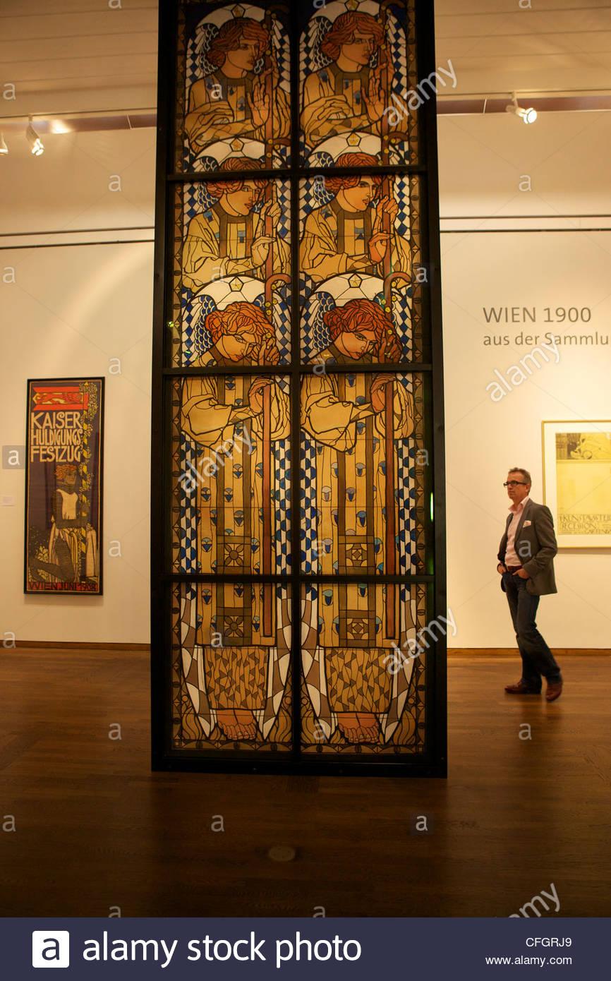 A man gazes at Koloman Moser's 'Design for the Angel Window.' - Stock Image