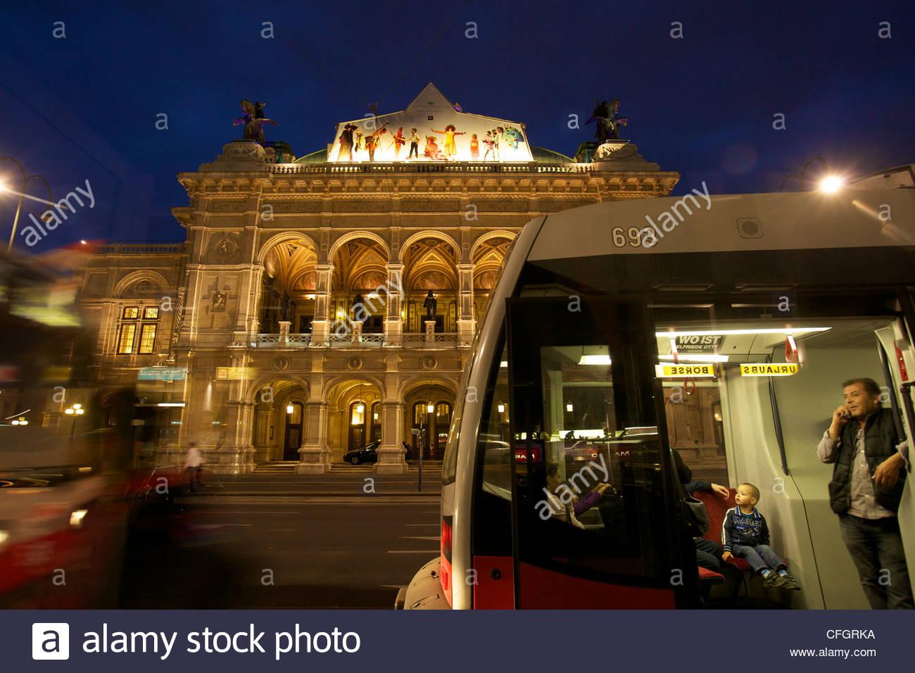 Tram passengers view the neo-renaissance Vienna State Opera at night. - Stock Image