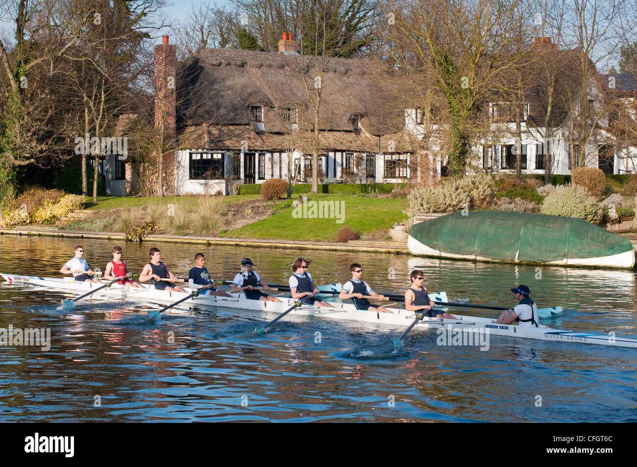 Rowing team go past picturesque thatched cottage at Fen Ditton, Cambridgeshire, England. - Stock Image