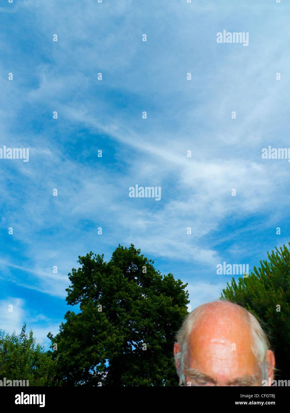 Sunny day, blue sky, elderly man in his back garden, Portrait format - Stock Image