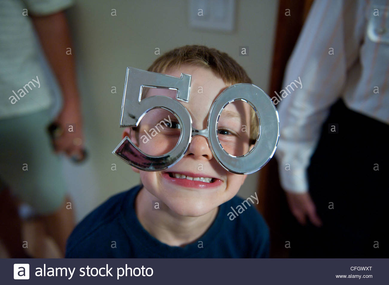 A young boy wears goofy glasses at a 50th birthday party celebration. - Stock Image