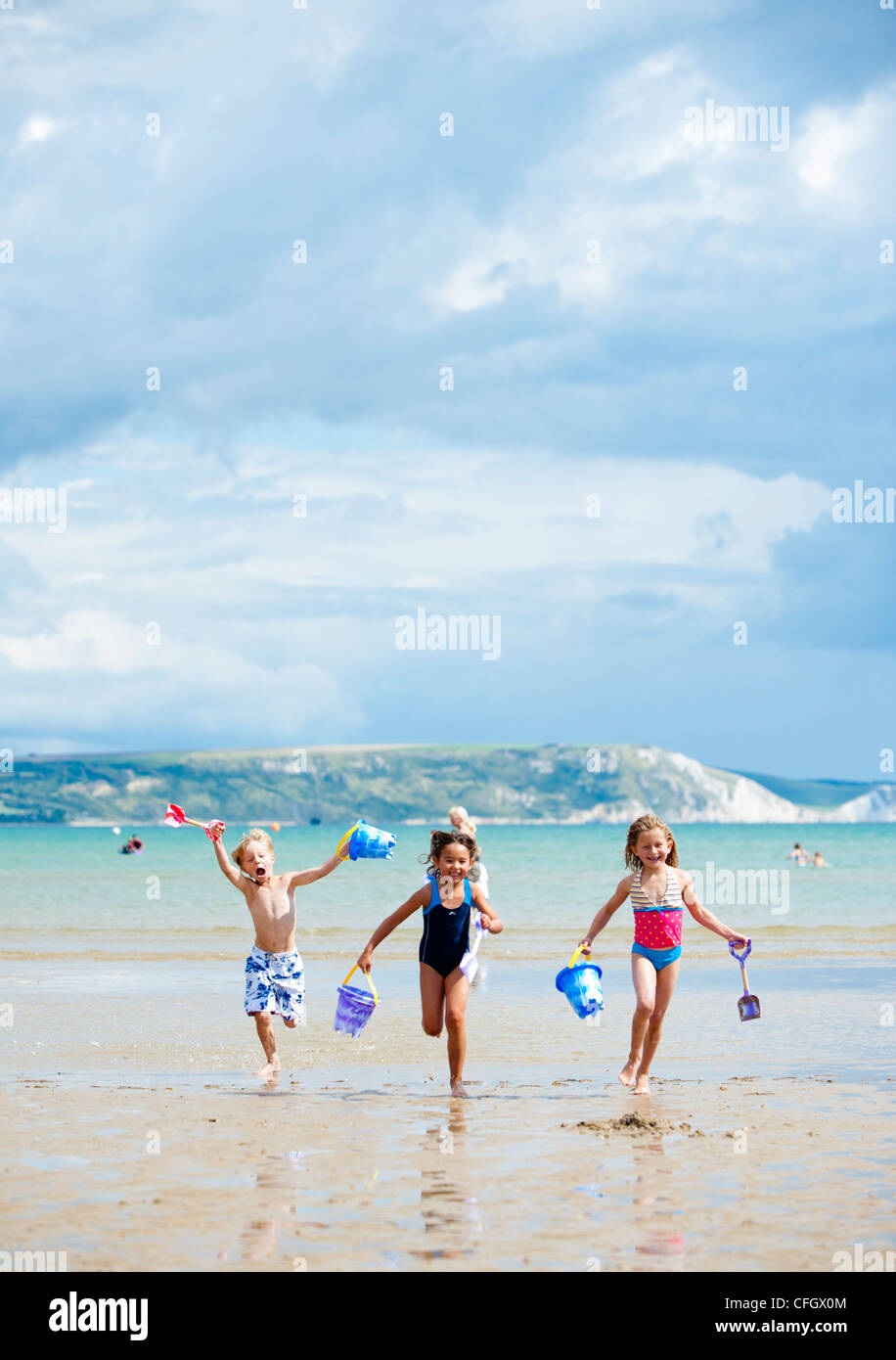 Children running on Weymouth beach, Dorset in summer - Stock Image