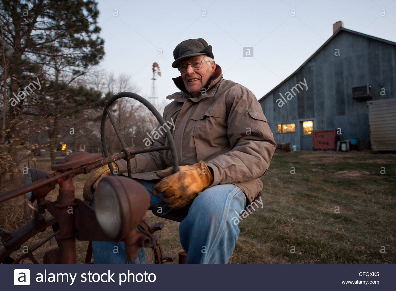 An elderly man sits on an antique tractor on a farm in Cortland, NE. - Stock Image