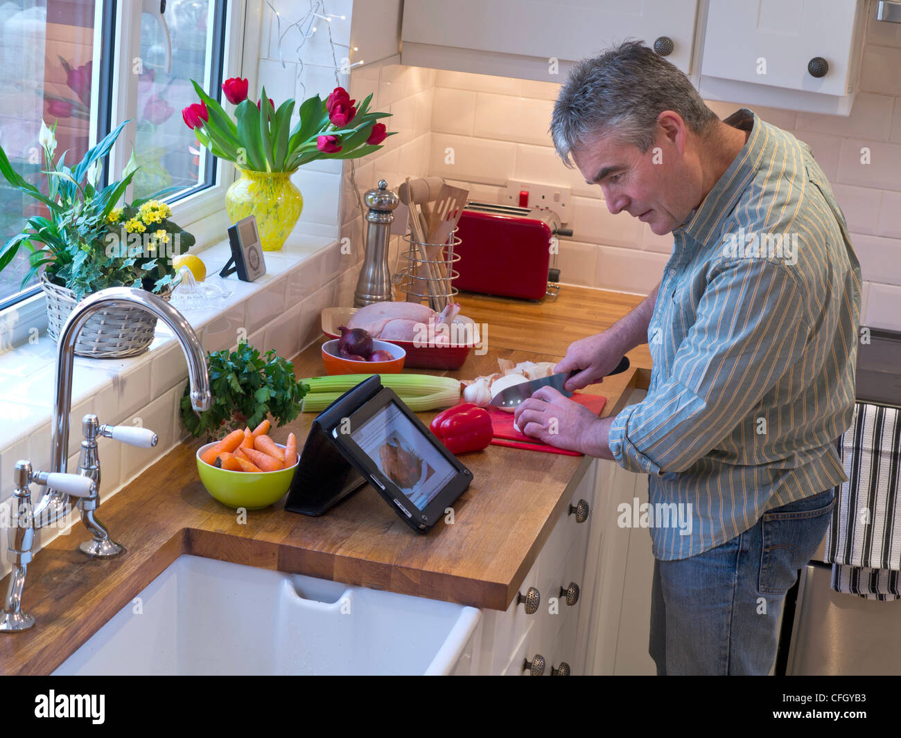 Man preparing meal in contemporary home kitchen using iPad tablet computer to provide recipe and reference guide - Stock Image