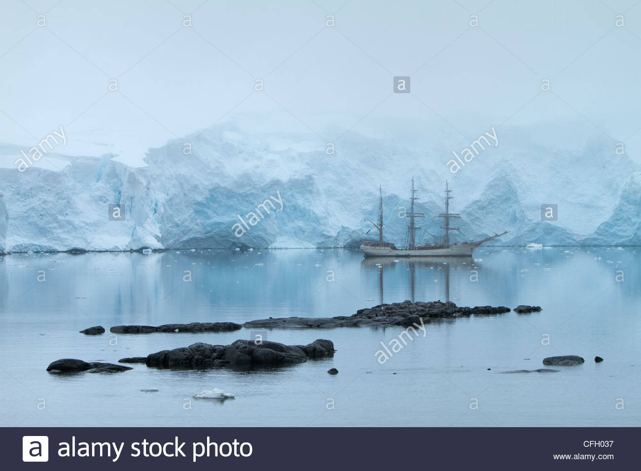 A barque at anchor in a calm inlet. - Stock Image