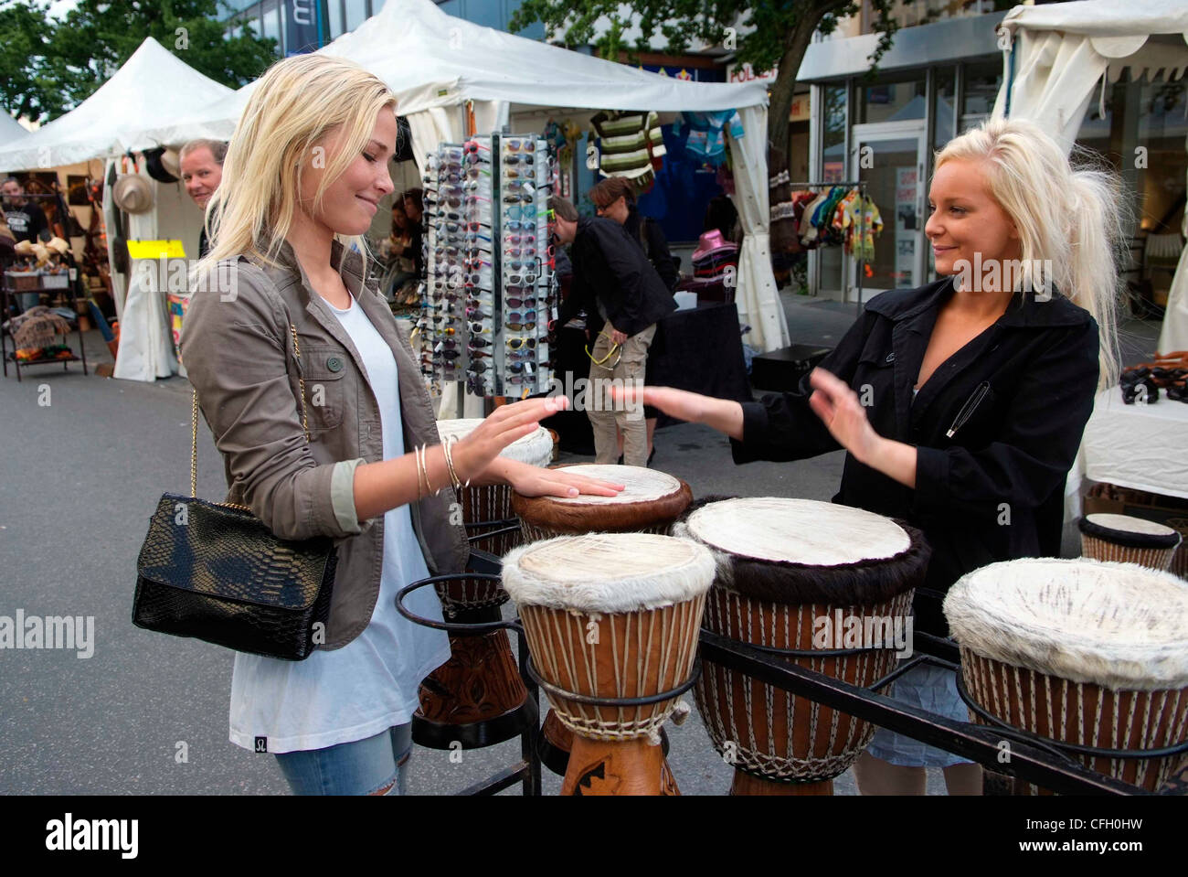 NORWAY Molde young blonde Norwegian women try out African drums in Molde market - Stock Image