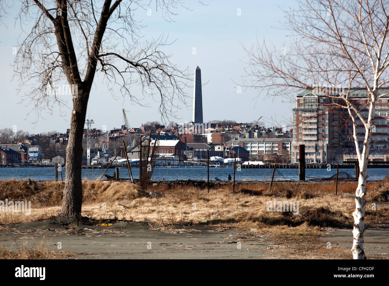 The Bunker Hill Monument is seen behind a vacant lot on the East Boston water, Boston, Massachusetts - Stock Image