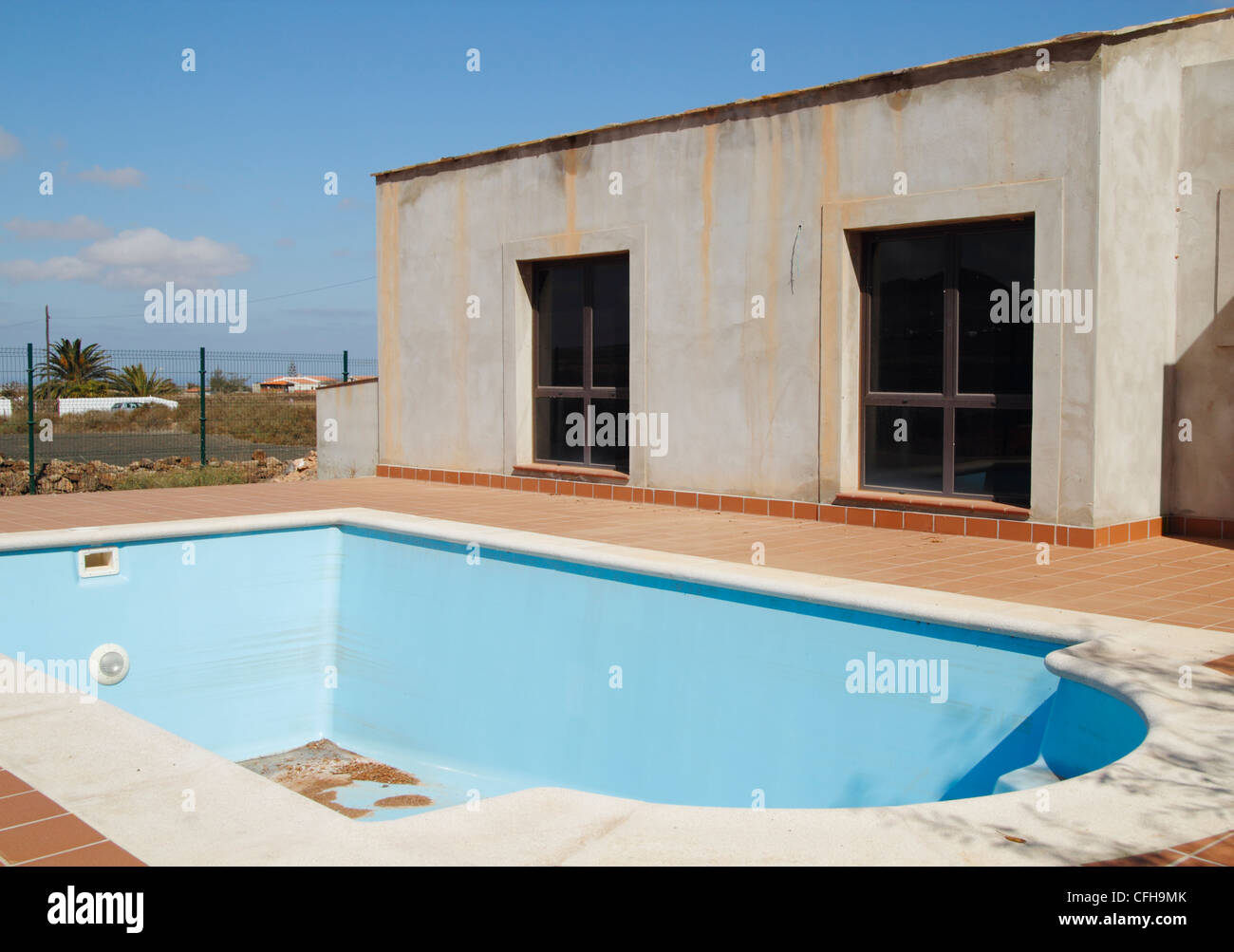 Empty swimming pool next to house at unfinished/abandoned building ...
