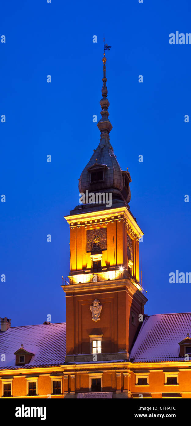 Illuminated clock tower of the Royal Castle in Castle Square, Old Town, Warsaw, Poland, at twilight. - Stock Image