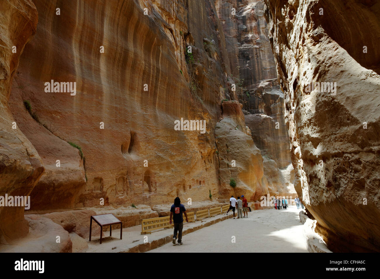 Petra. Jordan. View of tourists walking through the narrow ravine known as the Siq which gives spectacular introduction Stock Photo