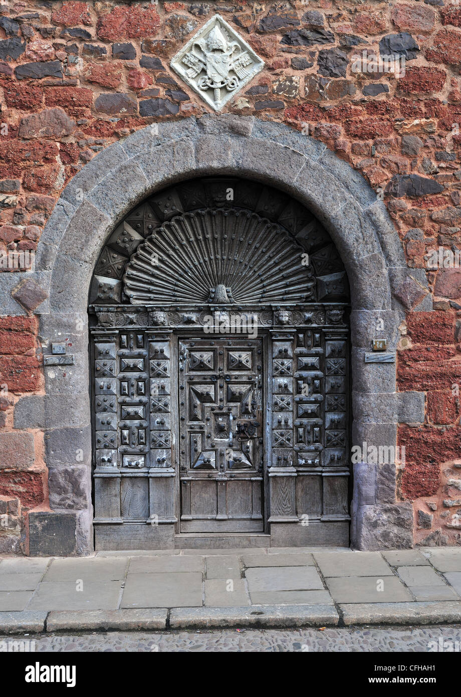 Ancient wooden door in a wall of Old Red Sandstone. Part of the Cathedral Close in Exeter, Devon, England - Stock Image