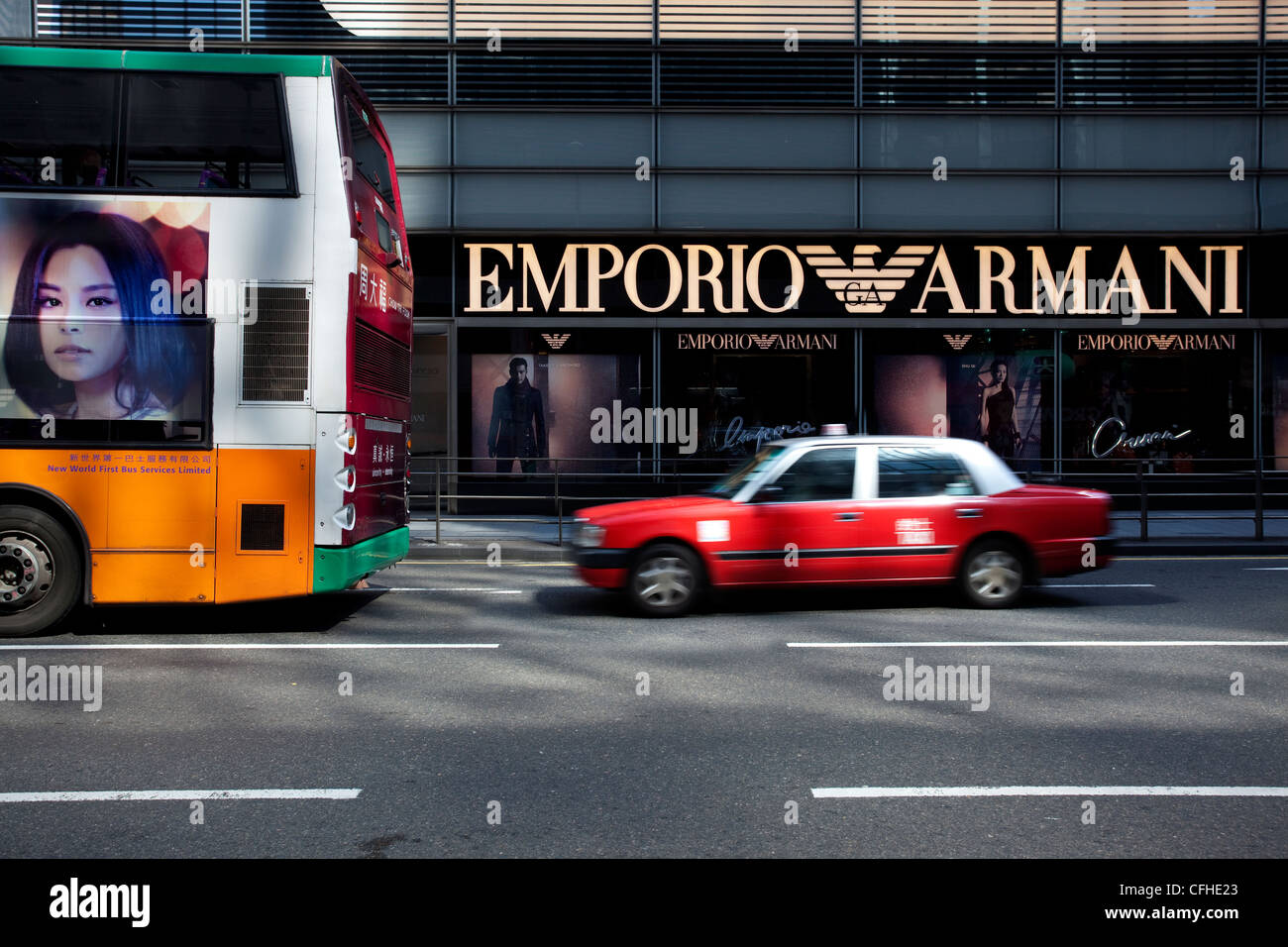 Bus and red taxi outside Emporio Armani store in Hong Kong - Stock Image