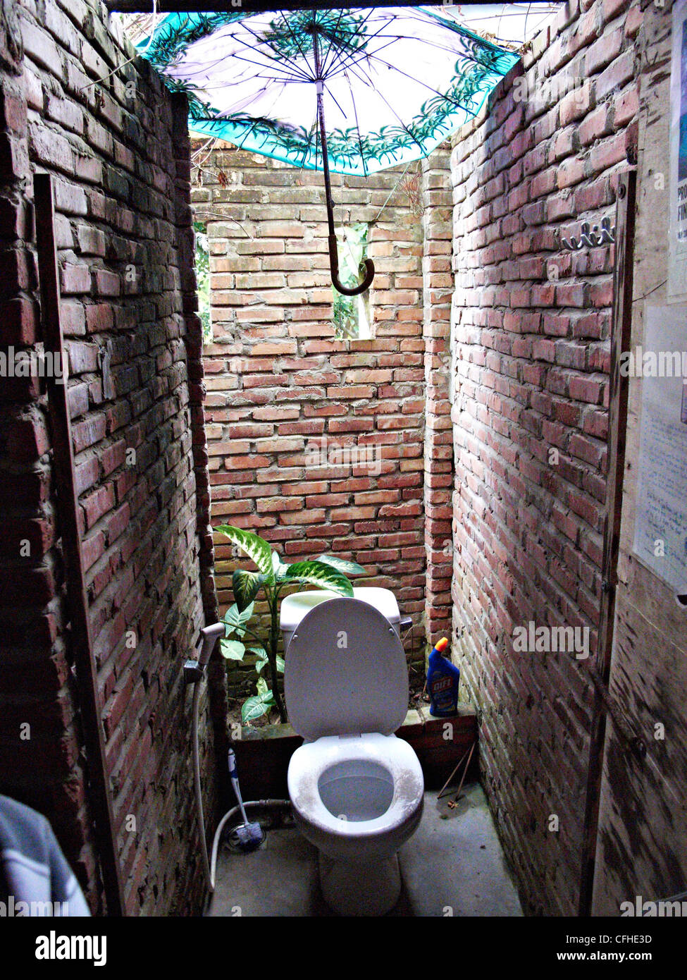 an umbrella is used as a roof in this toilet cubicle in Vietnam - Stock Image