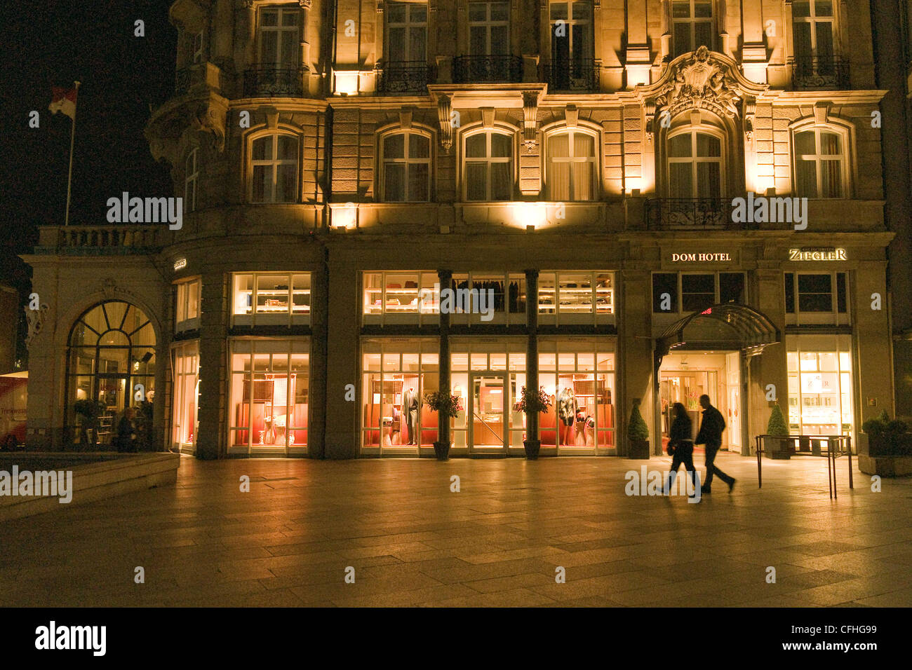 A couple walking at nght in the square near the Dom (cathedral) in Cologne, Germany - Stock Image