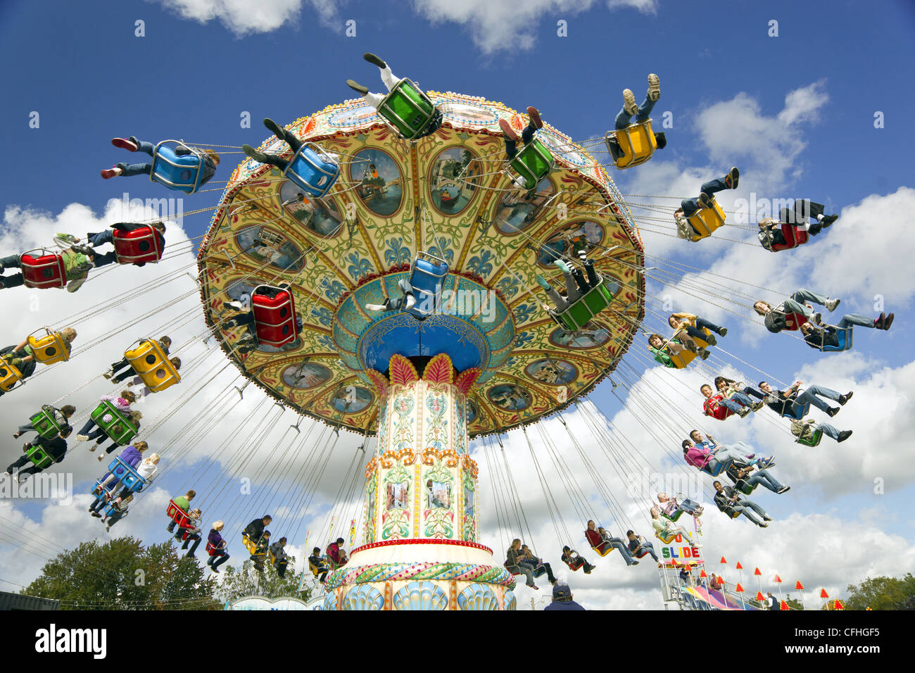 Families enjoying an amusement park ride at a carnival - Stock Image