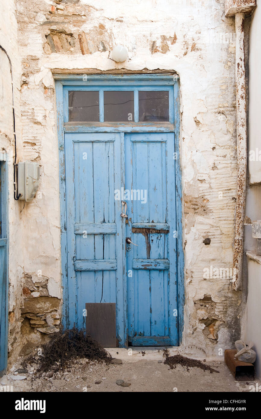 Old wooden double blue door with peeling paint in Marpissa, on the Greek Cyclade island of Paros. - Stock Image