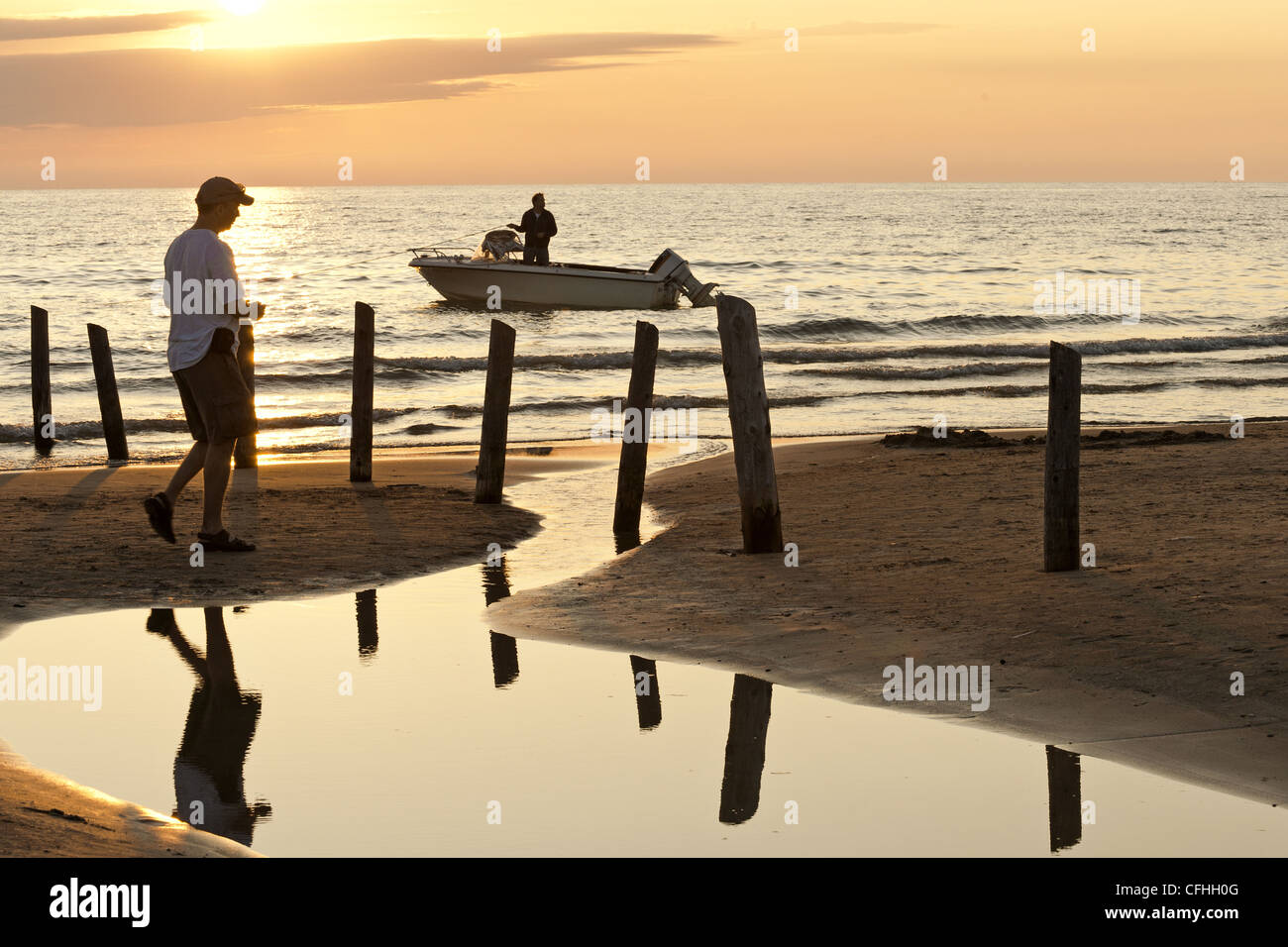 Walking on a beach at sunset, Lake Huron, Sauble Beach, ON, Canada - Stock Image