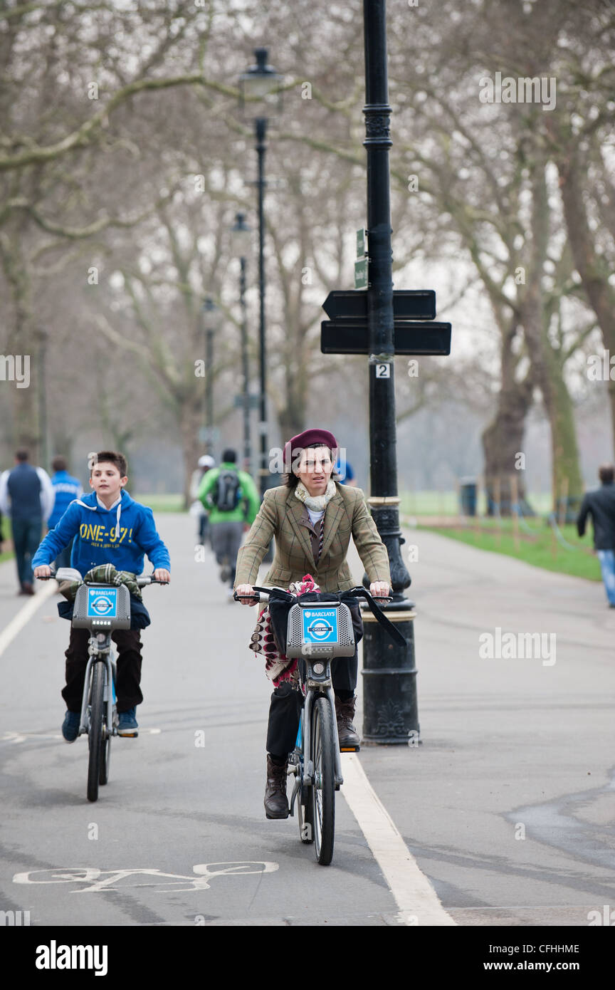 Two cyclists riding through Hyde Park in London - Stock Image