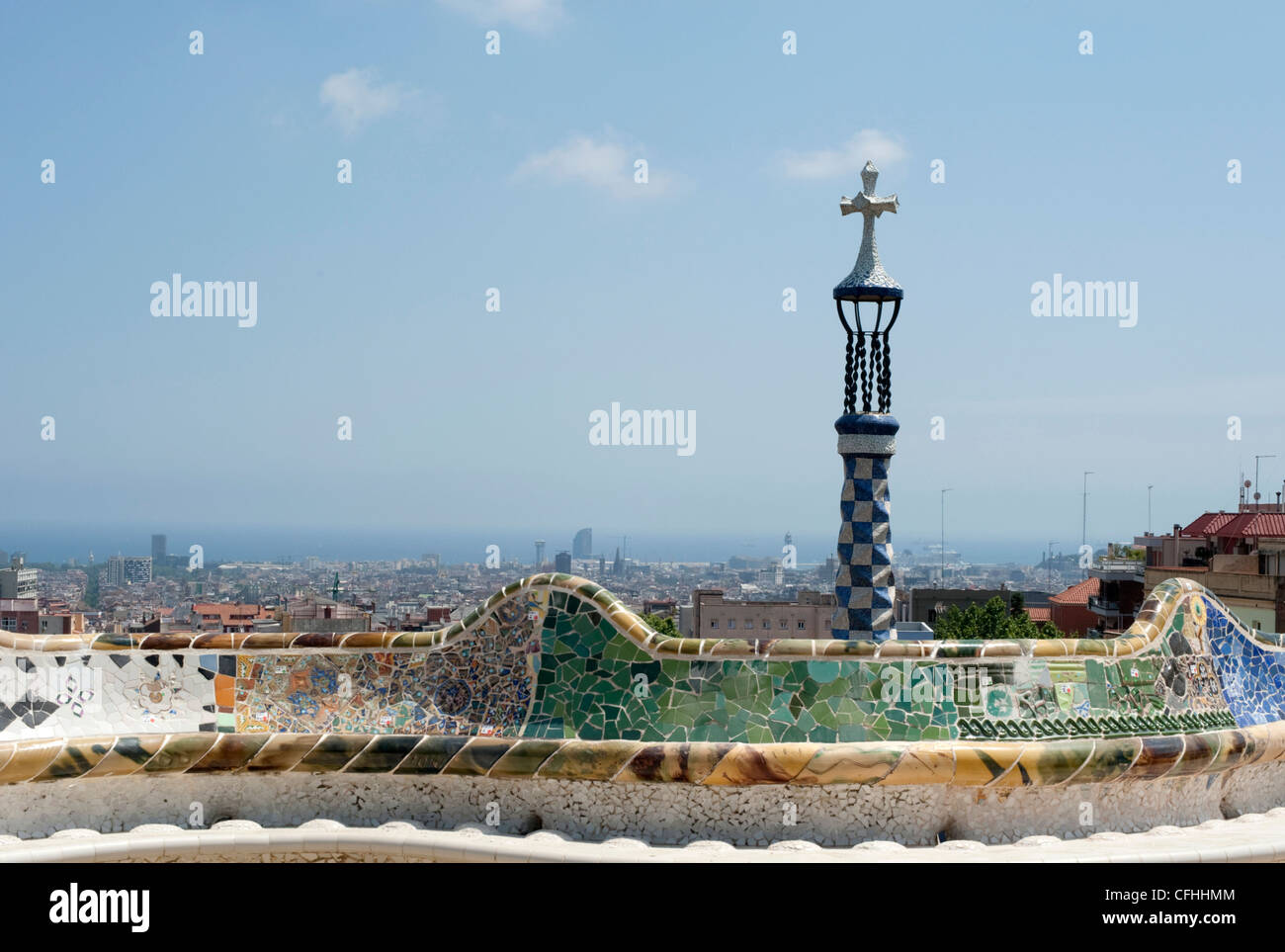The sea serpent tiled mosaic bench in the main terrace of Park Guell with a cross and Barcelona in the distance. - Stock Image