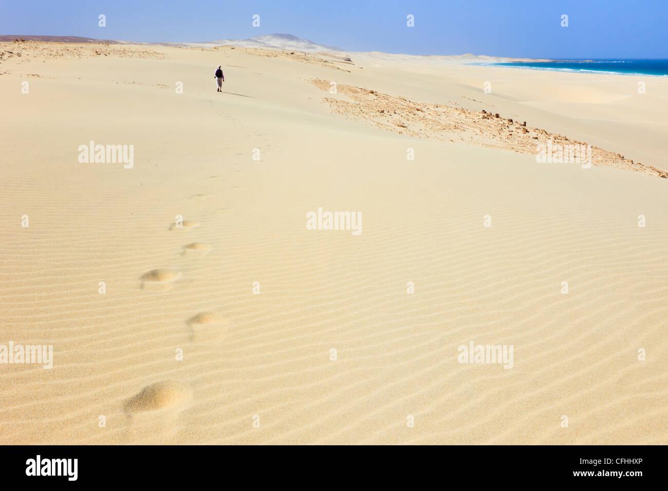 Person walking on sand dunes leaving footprints on white sandy beach of Praia de Chaves, Rabil, Boa Vista, Cape - Stock Image
