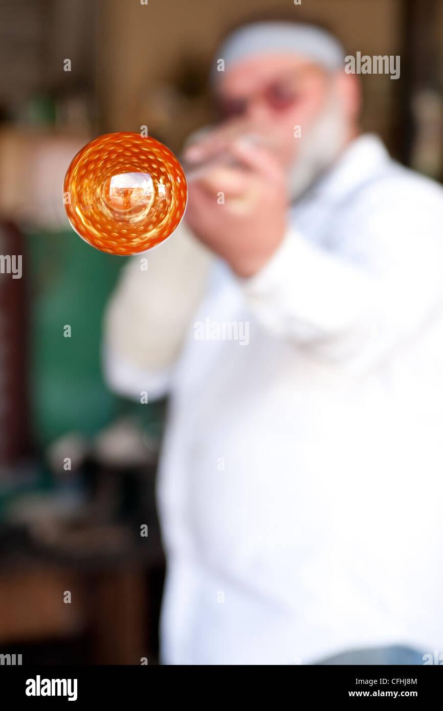 Glass blower, glassblower shaping molten glass - Stock Image