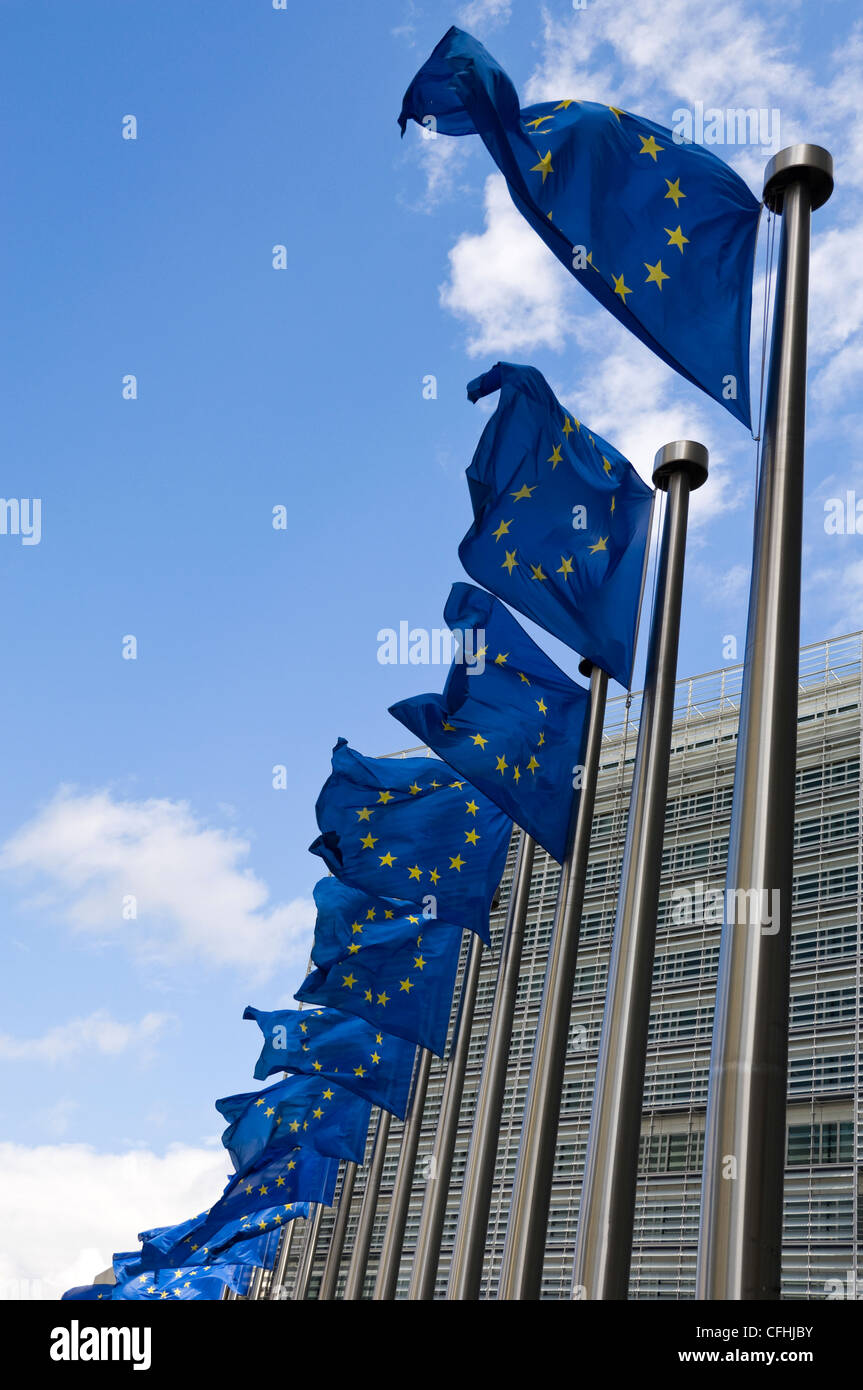 Vertical close up of many distinctive European Union flags at full mast outside the Berlaymont building in central - Stock Image