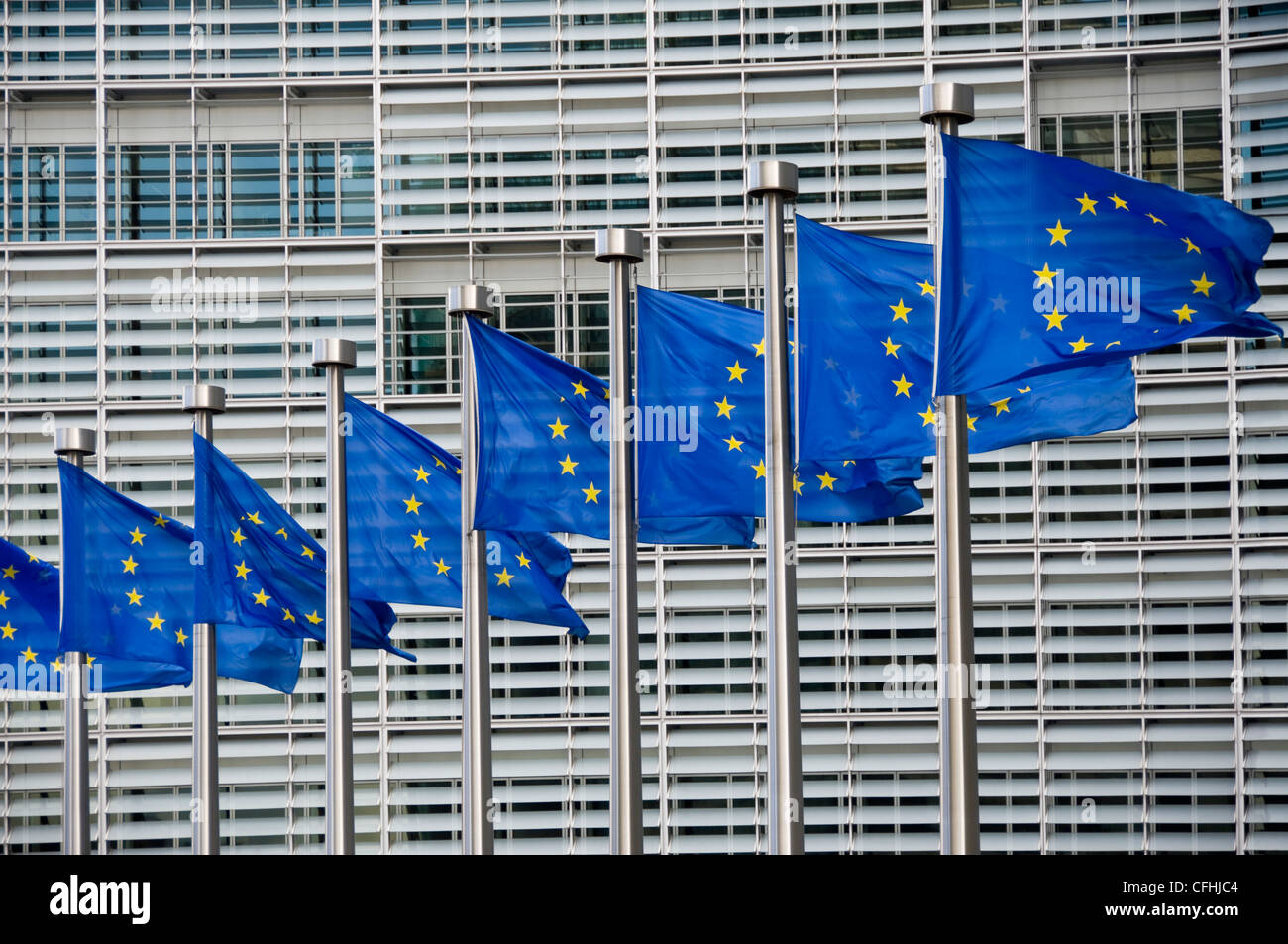 Horizontal close up of distinctive European Union flags at fullmast flying outside the Berlaymont building in central - Stock Image