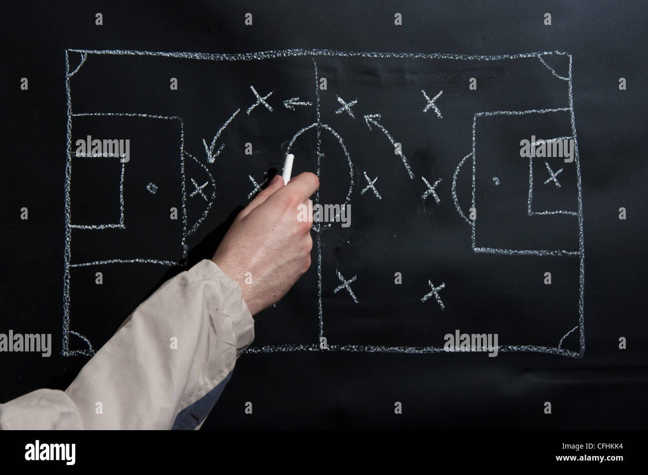 Man drawing a soccer game tactics and strategy with white chalk on a blackboard. - Stock Image