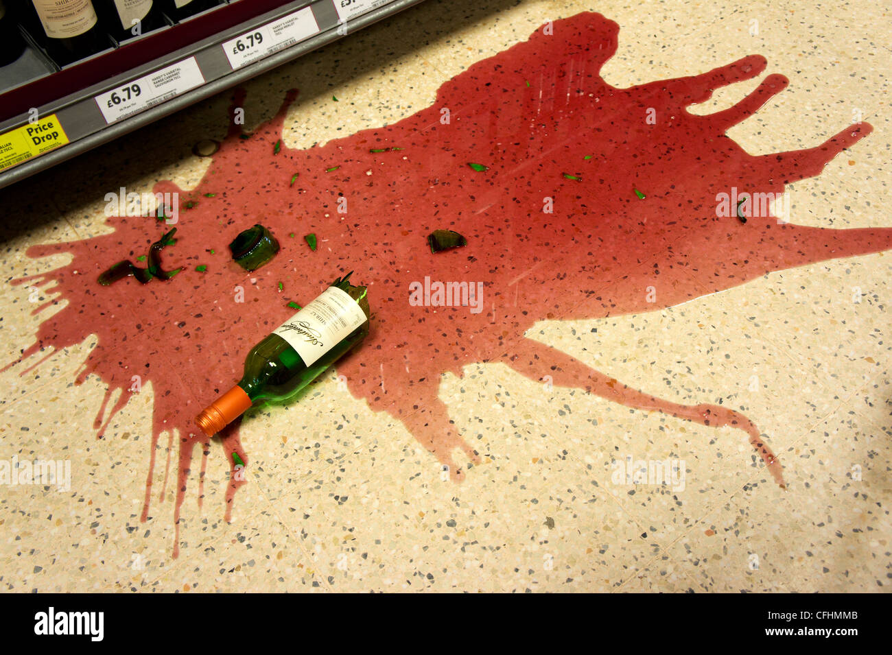 A bottle of Red Wine that has been dropped and smashed on the floor of a Supermarket - Stock Image