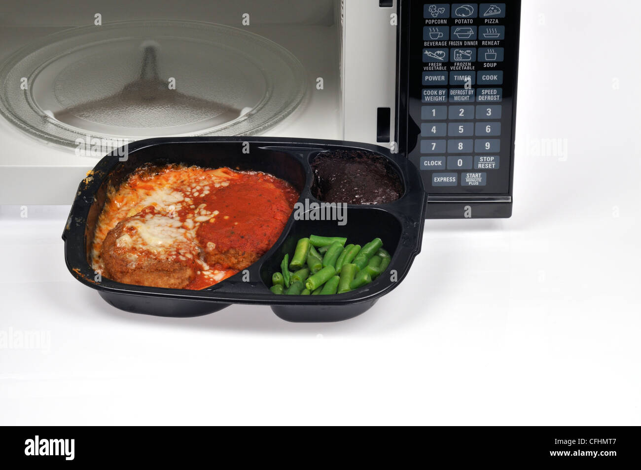 Cooked veal parmigiana readymeal tv dinner with green beans and dessert brownie in front of microwave oven with - Stock Image