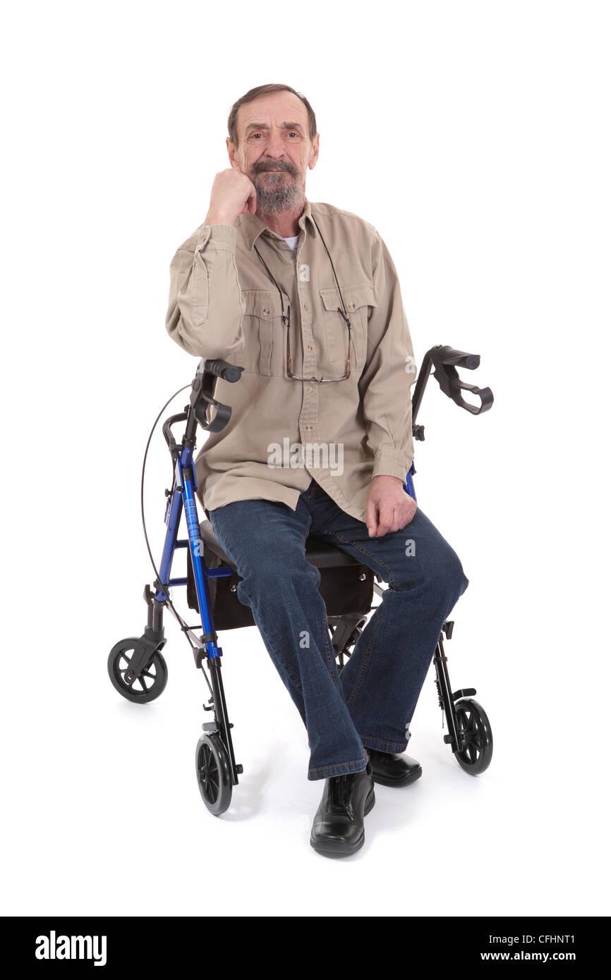 senior man sitting on disability walker on white background - Stock Image