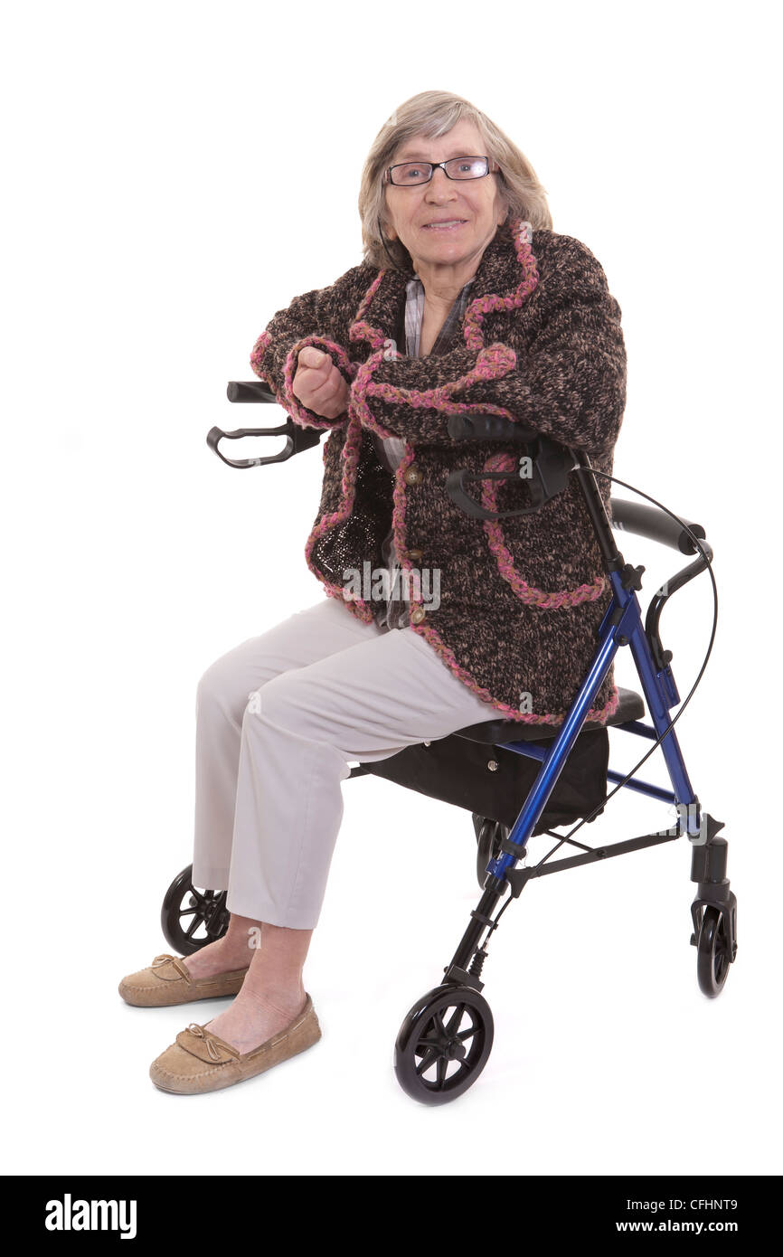 retired elderly woman sitting on disability walker - Stock Image