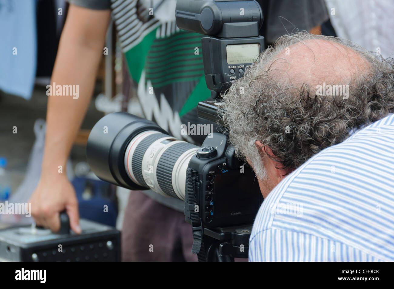 Back of a professional male Photographer with bald patch and grey hair shooting a Canon DSLR with l Zoom Lense  - Stock Image
