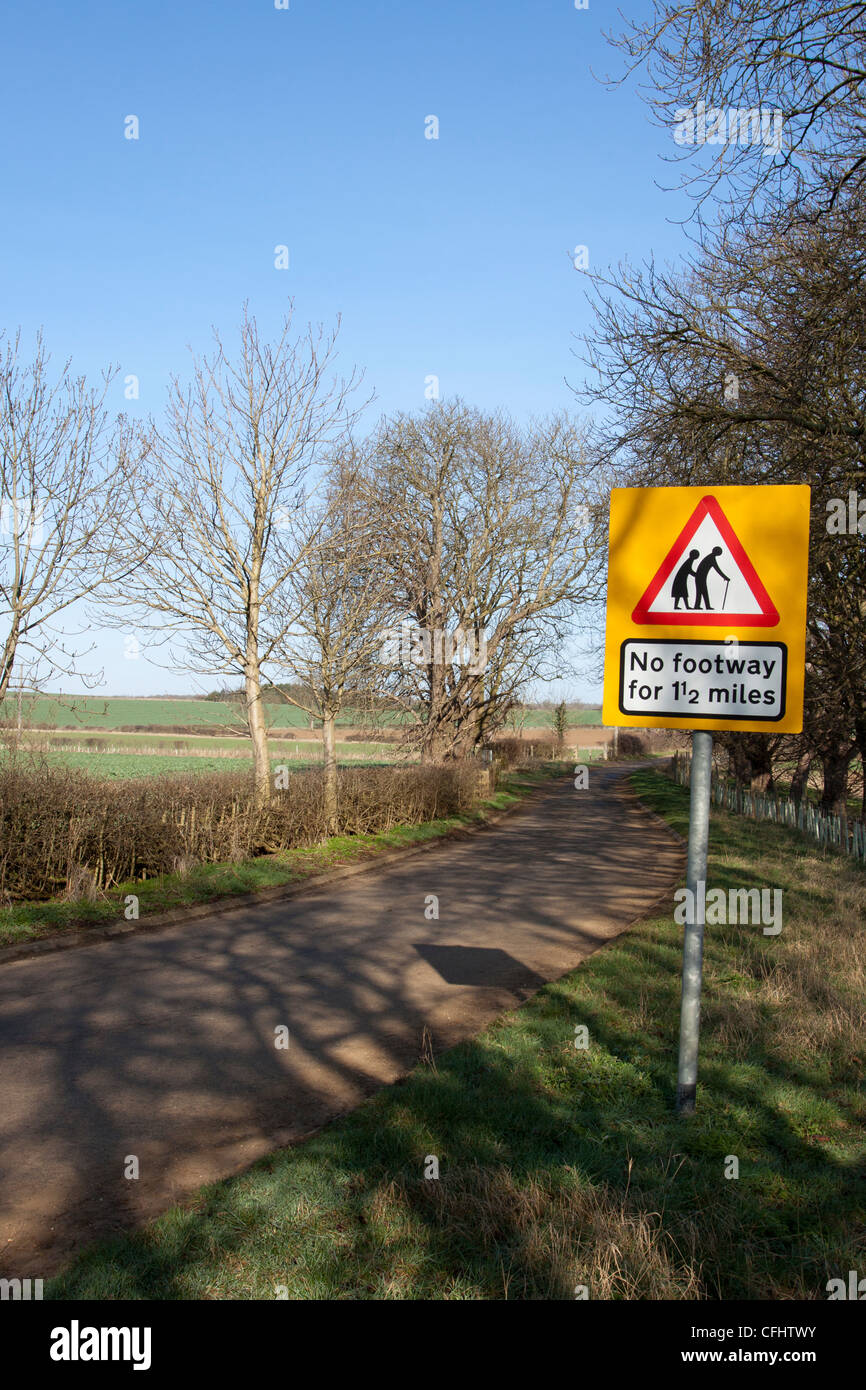 English countryside road with a no path warning sign.  The sign reads no footway 1 1/2 miles, Rutland, England, - Stock Image