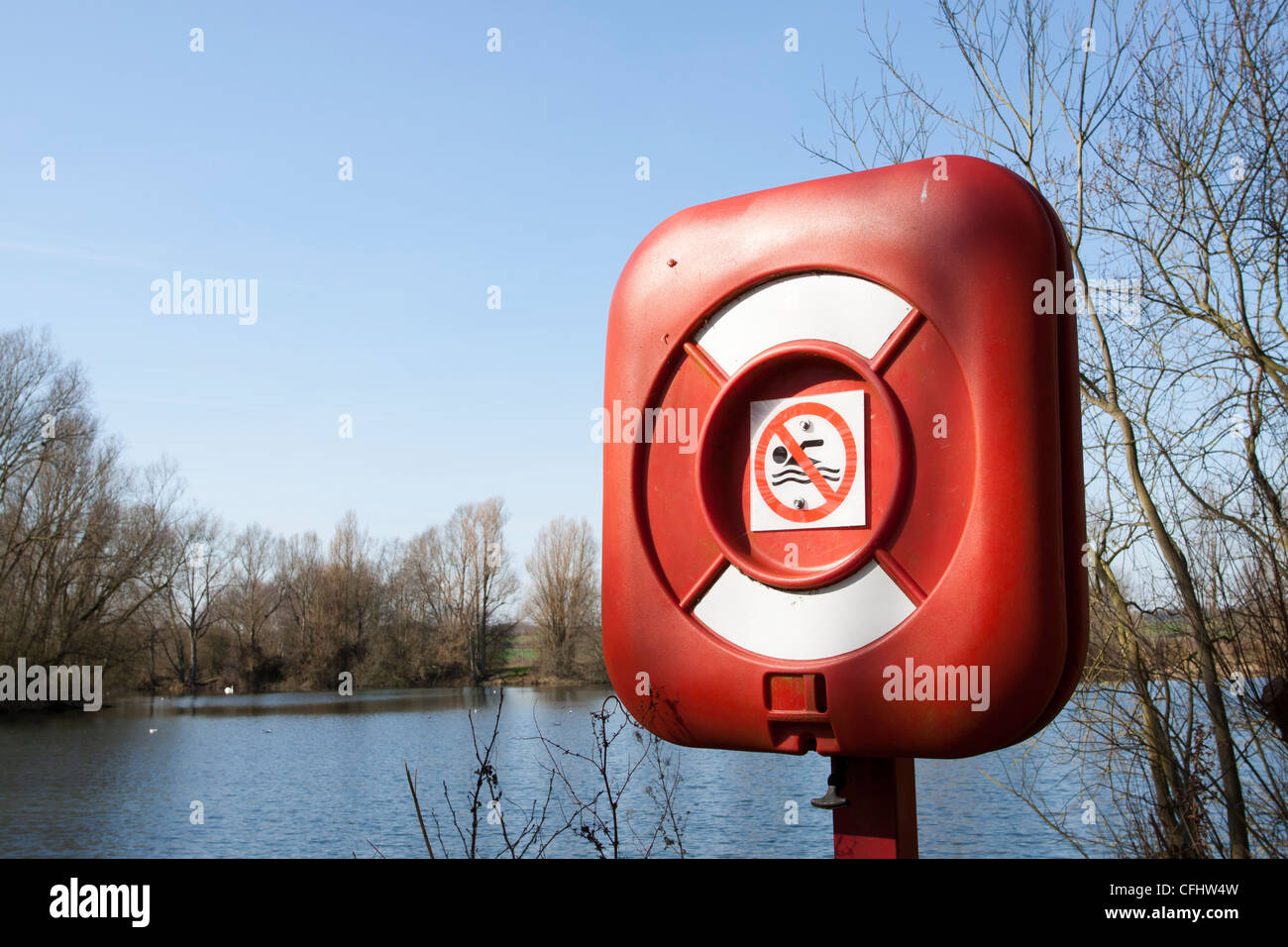 Red life saving equipment with a no swimming sign beside a pond/lake Northamptonshire, England, UK - Stock Image