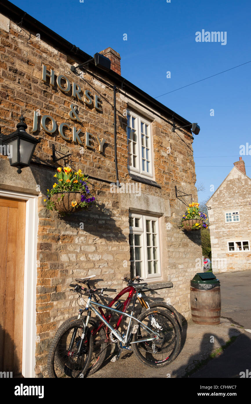 Mountain bikes outside The Horse and Jockey public house, Manton, Rutland, England, UK - Stock Image
