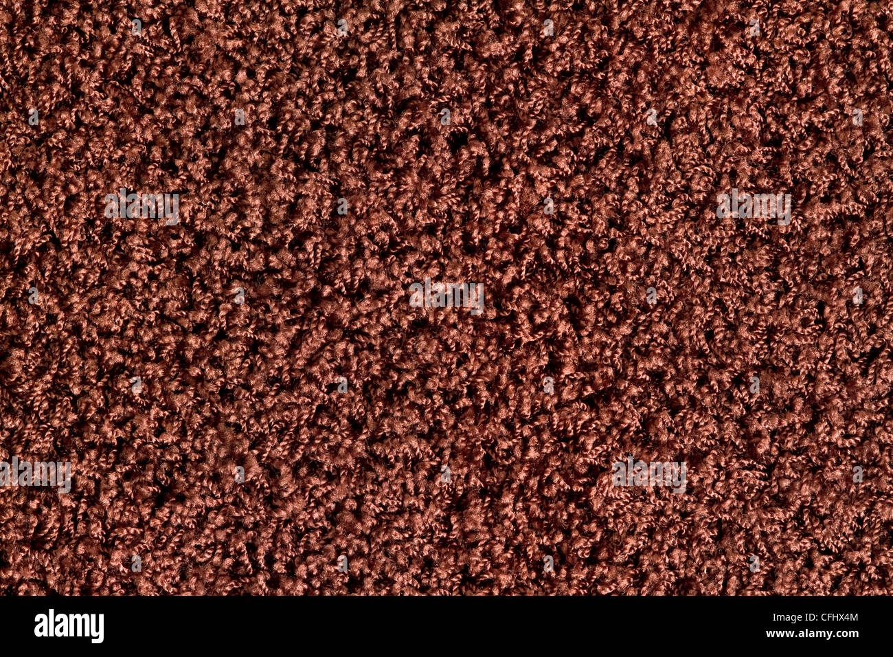 texture of a colored carpet with long brown pile. - Stock Image