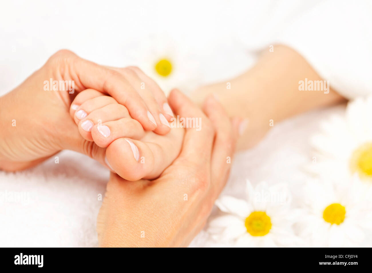 Female hands giving massage to soft bare foot - Stock Image