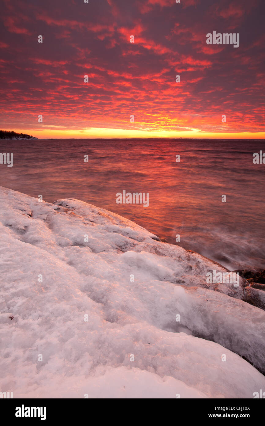 Icy coastline and colorful skies at dusk at Larkollen in Rygge, Østfold fylke, Norway. - Stock Image