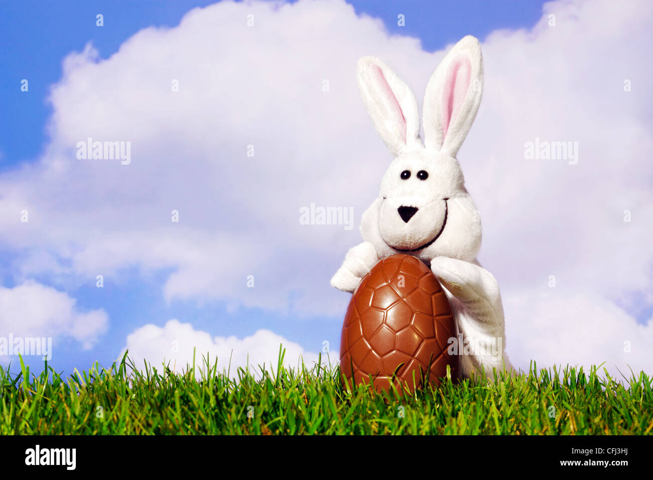 Fun photo of a white easter bunny puppet holding a large chocolate egg on grass with a blue cloudy sky background. Stock Photo